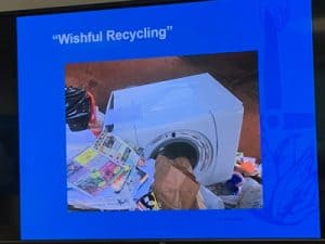 Picture of a washing maching being put in with recyclables.